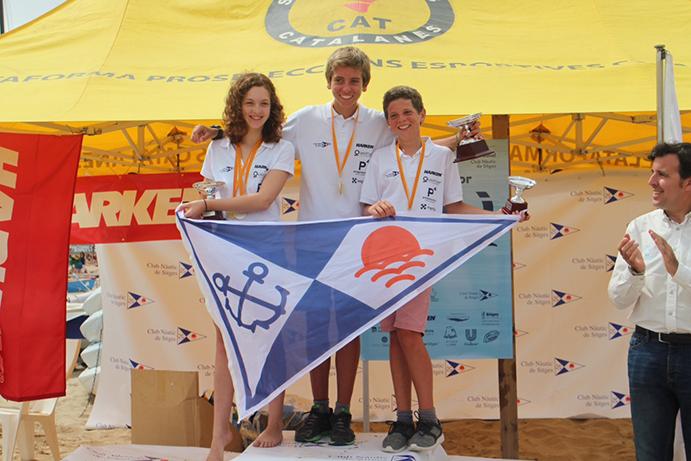 Dani Vilardell en lo alto del podio del Campeonato de Cataluña junior 2016. La segunda clasificada es Joana Meyer y el tercero es su hermano, Eric Vilardell. Los tres navegan por el Club Nàutic Sitges.
