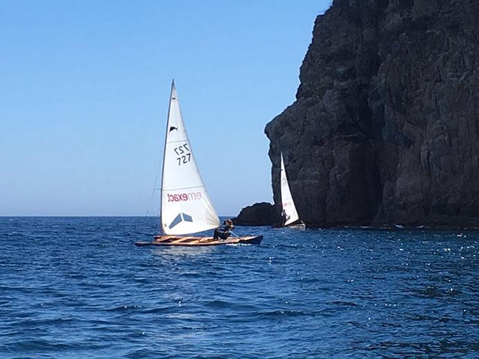 Los navegantes del club amfitirión saben cque cuando sopla de garbí hay que ir a lamer las altas paredes de la Punta de Cala Pedrosa. En la imagen, puede verse en primer plano a Nina Esteba y al fondo, virando, a su padre, Quim Esteba.