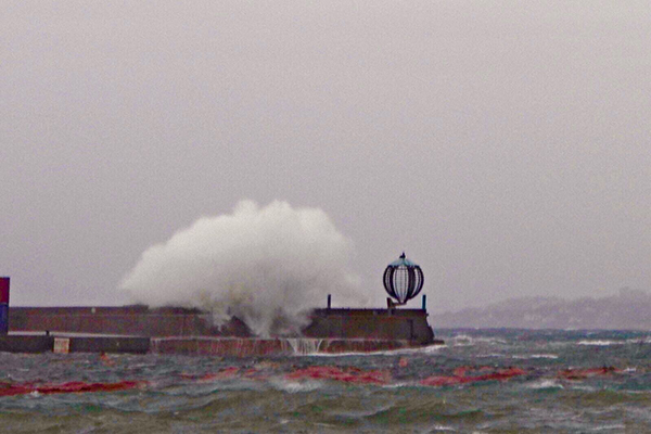 Una ola rompe contra el espigón de la bocana del puerto de Palamós y lo supera. Foto cedida por Jordi Sabater.
